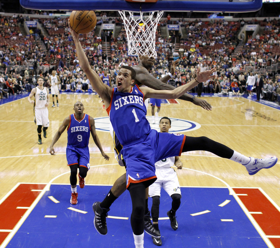 Photo - Philadelphia 76ers' Michael Carter-Williams (1) goes up to shoot against Utah Jazz's Marvin Williams during the first half of an NBA basketball game on Saturday, March 8, 2014, in Philadelphia. (AP Photo/Matt Slocum)