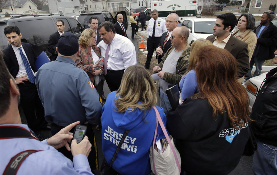 "New Jersey Gov. Chris Christie, center left, greets residents in Union Beach, N.J., Tuesday, Feb. 5, 2013, outside a center where Federal Emergency Management Agency and state agencies were helping with claims. Christie says the National Flood Insurance Program's handling of claims in New Jersey has been ""a disgrace,"" complaining that the program has been far too slow to resolve claims from Superstorm Sandy, with 70 percent of cases unresolved three months after the disaster. (AP Photo/Mel Evans)"