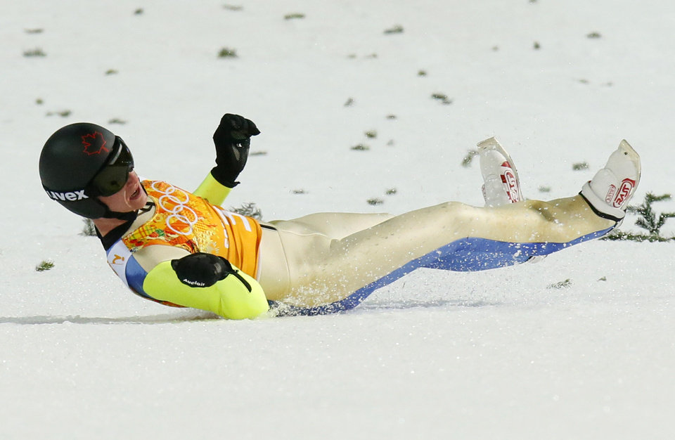 Photo - Canada's Matthew Rowley slides after falling during the ski jumping large hill team competition at the 2014 Winter Olympics, Monday, Feb. 17, 2014, in Krasnaya Polyana, Russia. (AP Photo/Dmitry Lovetsky)