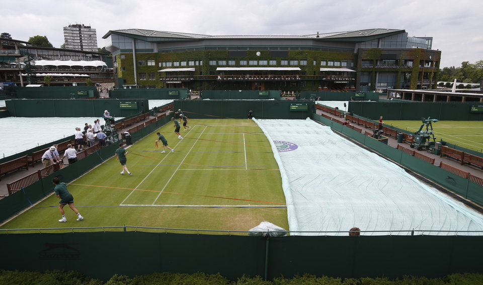 Photo - Court covers practice covering the outside courts with the iconic Centre Court in the background, as preparations continue for the  All England Lawn Tennis Championships in Wimbledon, London, Sunday, June  22, 2014. The Championships start Monday June 23 . (AP Photo/Pavel Golovkin)