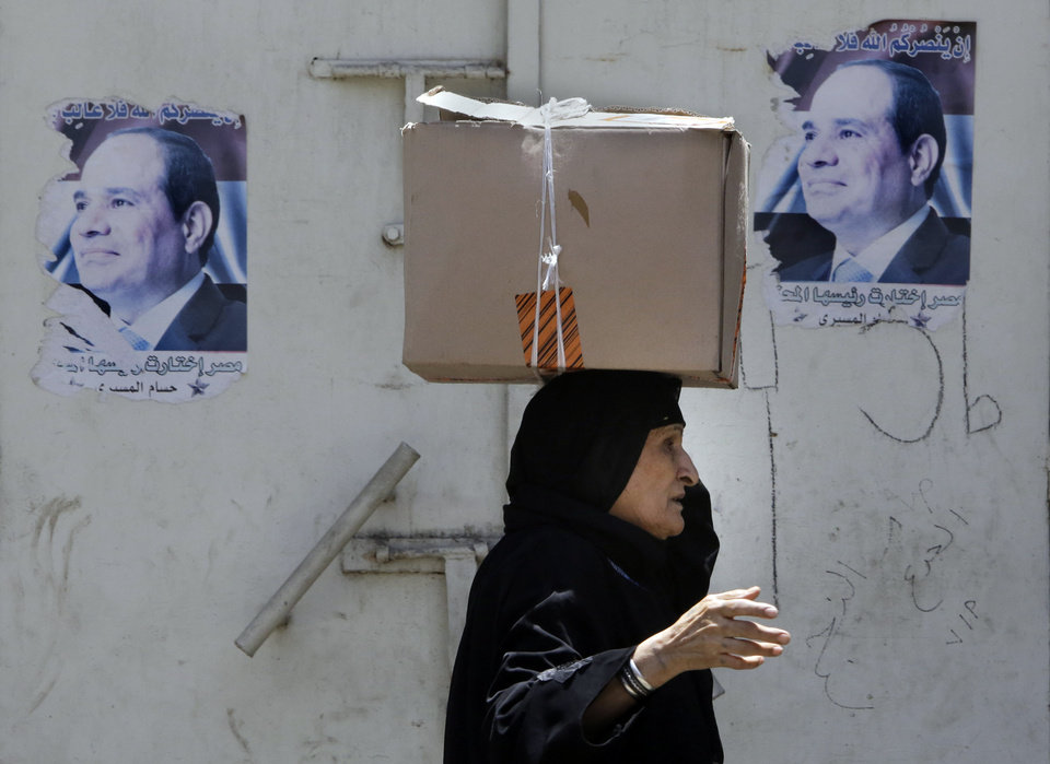 Photo - An elderly Egyptian vendor walks past old election posters supporting newly elected President Abdel-Fattah el-Sissi in Cairo, Egypt, Saturday, July 5, 2014. El-Sissi, elected to office last month, has said he will need to tackle the tough issue of subsidies that eat up nearly a quarter of the state budget and asked every Egyptian to be ready to sacrifice to help the country's battered economy after three years of turmoil. The country's successive leaders have balked at reducing them because half of the country's 85 million people live at or below the poverty line of $2 a day and rely on government subsidies of wheat and fuel for survival. (AP Photo/Amr Nabil)