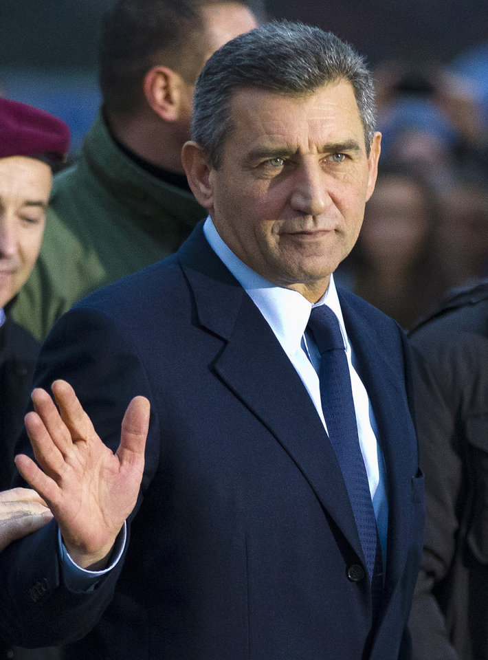 Photo -   Croatian Gen. Ante Gotovina waves as he arrives to the airport in Zagreb, Croatia, Friday, Nov. 16, 2012. The Yugoslav war crimes tribunal overturned the convictions of two Croat generals on Friday for murdering and illegally expelling Serb civilians in a 1995 military blitz, and ordered both men to be freed immediately. (AP Photo/Nikola Solic)