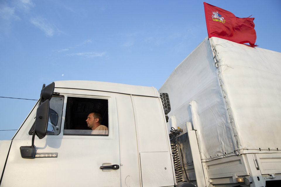 Photo - A white truck with humanitarian aid is driven from Voronezh towards Rostov-on-Don, Russia, early Thursday, Aug. 14, 2014. Russia on Tuesday dispatched some hundreds of trucks, although only a small proportion were counted in this convoy, covered in white tarps and sprinkled with holy water on a mission to deliver aid to a rebel-held zone in eastern Ukraine. (AP Photo/Pavel Golovkin)