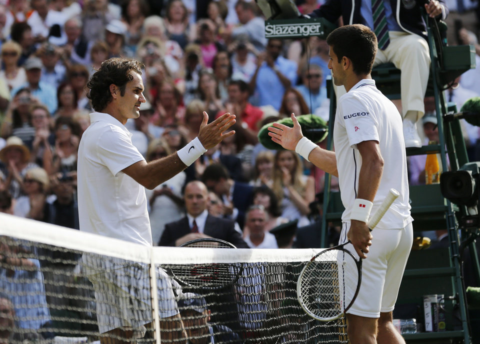 Photo - Novak Djokovic of Serbia, right, shakes hands after defeating Roger Federer of Switzerland in the men's singles final at the All England Lawn Tennis Championships in Wimbledon, London, Sunday July 6, 2014. (AP Photo/Ben Curtis)