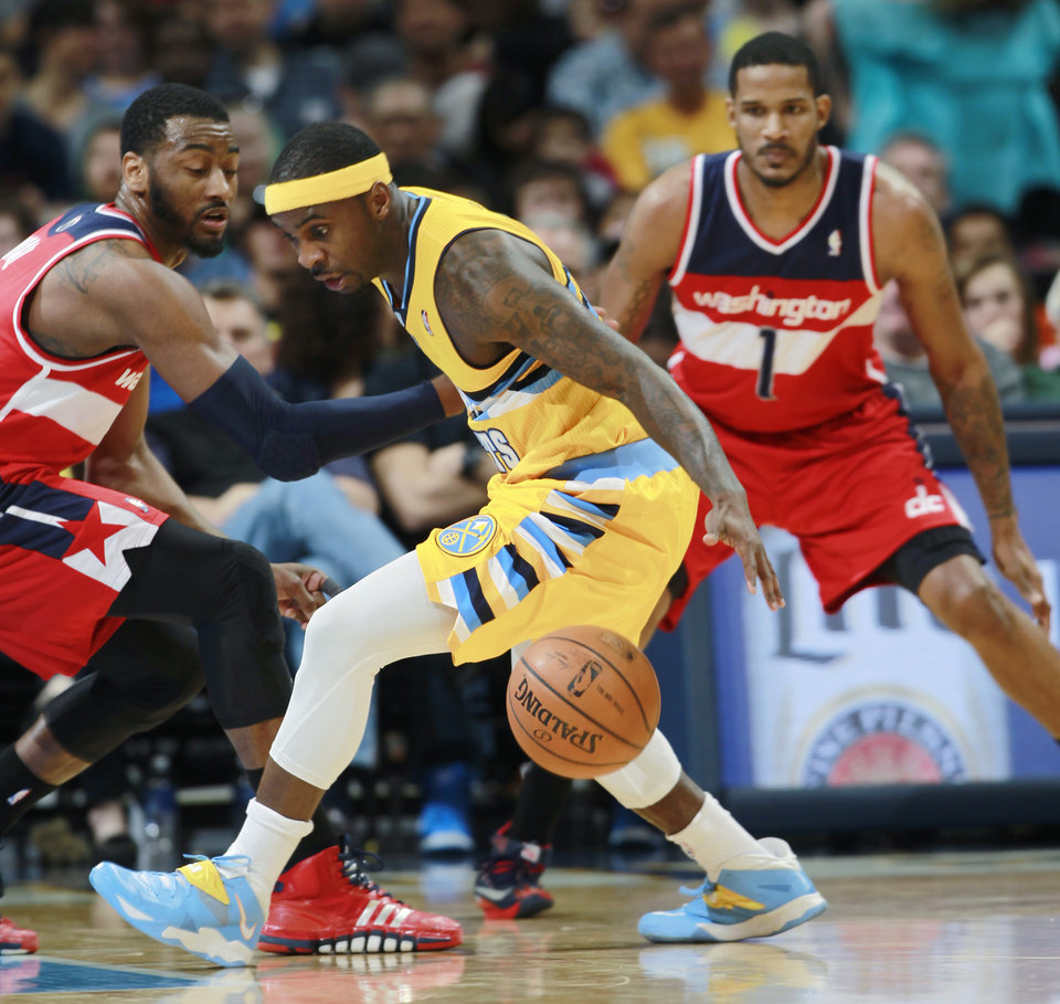 Photo - Denver Nuggets guard Ty Lawson, center, loses control of the ball as Washington Wizards guard John Wall, left, and forward Trevor Ariza cover in the first quarter of an NBA basketball game in Denver on Sunday, March 23, 2014. (AP Photo/David Zalubowski)