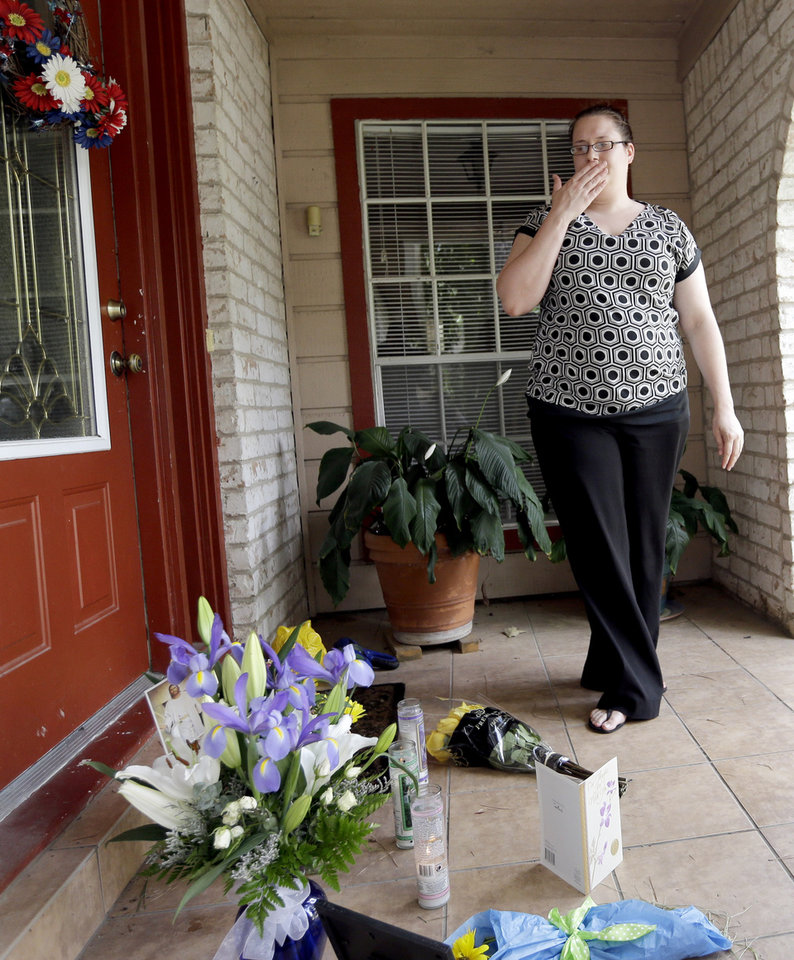 Photo - Neighbor Kristen Breelove pauses after leaving flowers on the porch of a home Thursday, July 10, 2014, in Spring, Texas. where six family members were shot to death the night before. he Harris County Sheriff's Office says Ronald Lee Haskell was booked Thursday on a capital murder/multiple murders charge and held without bond. Authorities believe Haskell fatally shot two adults and four children on Wednesday night and critically wounded a 15-year-old girl, who called 911.  (AP Photo/David J. Phillip)