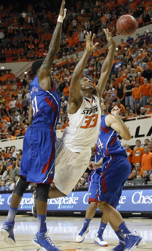 Photo - Oklahoma State 's Marcus Smart (33) is fouled on a shot by Kansas' Jamari Traylor (31) during the college basketball game between the Oklahoma State University Cowboys (OSU) and the University of Kanas Jayhawks (KU) at Gallagher-Iba Arena on Wednesday, Feb. 20, 2013, in Stillwater, Okla. Photo by Chris Landsberger, The Oklahoman