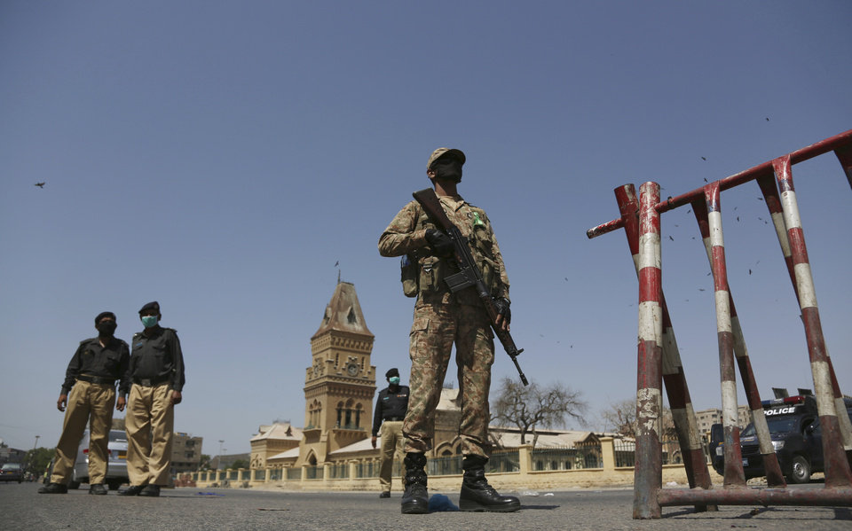 Photo -  Soldiers and police stand guard during a lockdown to help stop the spread of the coronavirus in Karachi, Pakistan, Friday, March, 3, 2020. Some mosques were allowed to remain open in Pakistan on Friday, the Muslim sabbath when adherents gather for weekly prayers, even as the coronavirus pandemic spread and much of the country had shut down. (AP Photo/Fareed Khan)