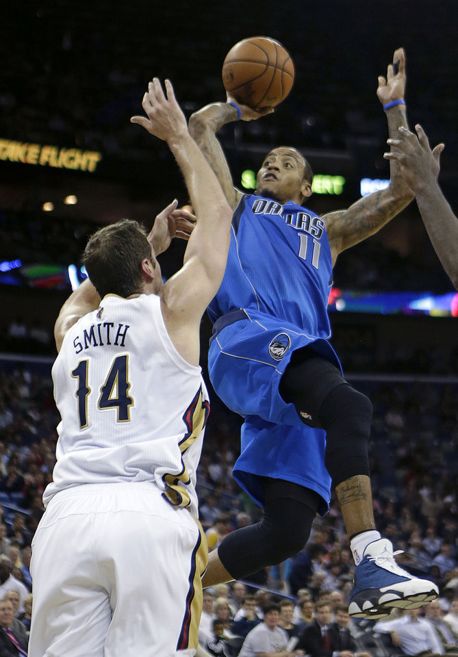 Photo - Dallas Mavericks shooting guard Monta Ellis (11) shoots over New Orleans Pelicans center Jason Smith (14) in the first half of an NBA basketball game in New Orleans, Wednesday, Dec. 4, 2013. (AP Photo/Gerald Herbert)