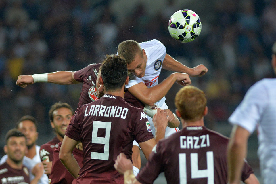 Photo - Inter Milan defender Nemanja Vidic, top right, jumps for the ball with Torino's Kamil Glik during a Serie A soccer match between Torino and Inter Milan at the Olympic stadium, in Turin, Italy, Sunday, Aug. 31, 2014. (AP Photo/Massimo Pinca)