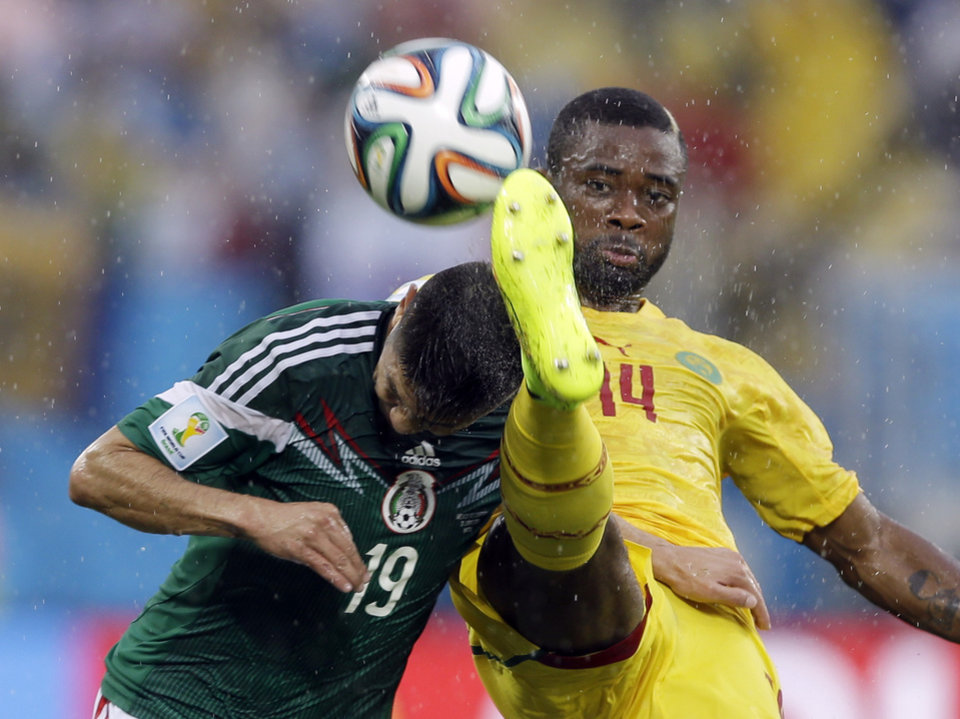 Photo - In this Friday, June 13, 2014 photo, Mexico's Oribe Peralta, left, and Cameroon's Aurelien Chedjou, battle for the ball during their group A World Cup soccer match in the Arena das Dunas in Natal, Brazil. Peralta scored in the 61st minute to help Mexico to a 1-0 victory Friday and the three points it needed to have any chance of advancing from a tough Group A at the World Cup. (AP Photo/Ricardo Mazalan)