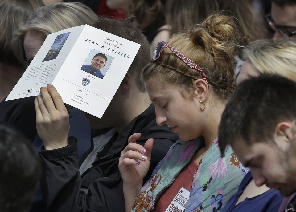 Mourners bow their heads during a memorial service for fallen Massachusetts Institute of Technology campus officer Sean Collier at MIT in Cambridge, Mass. Wednesday, April 24, 2013.  Collier was fatally shot on the MIT campus Thursday, April 18, 2013. Authorities allege that the Boston Marathon bombing suspects were responsible. (AP Photo/Elise Amendola)