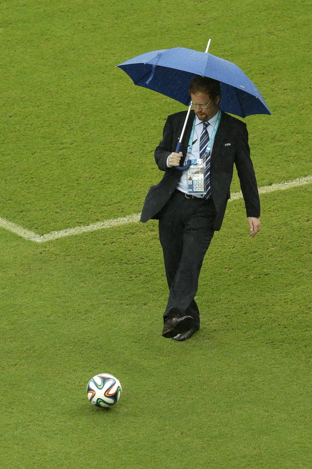 Photo - A FIFA official tests the pitch as rain pours down prior to the group G World Cup soccer match between the USA and Germany at the Arena Pernambuco in Recife, Brazil, Thursday, June 26, 2014. (AP Photo/Hassan Ammar)