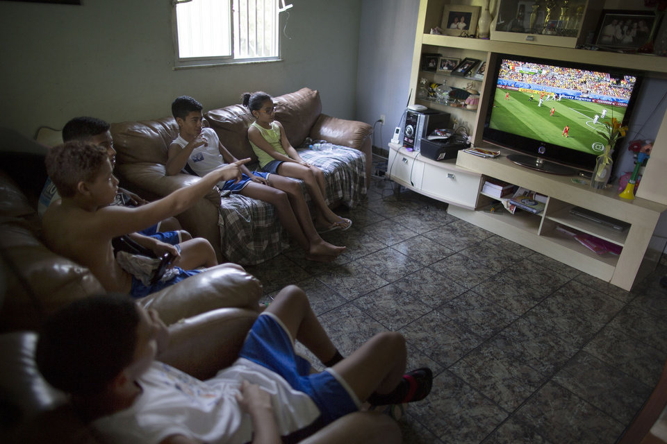 Photo - In this June 17, 2014 photo, Andre Rodrigues de Principe, 14, known as Andrezinho to his neighbors, second from right, watches a World Cup soccer match with his friend and sister at his home in the Vidigal slum of Rio de Janeiro, Brazil. Brazil's laws prohibit clubs from signing players younger than 16. But armies of scouts, agents and career managers, as well as plenty of impostors, dodge the rules to prey on families' hopes. (AP Photo/Leo Correa)