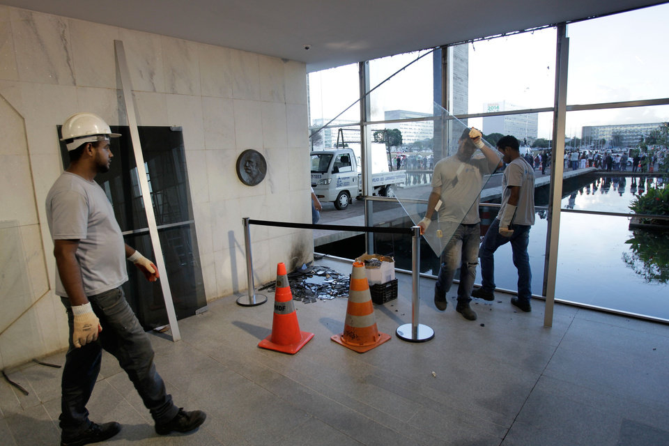 Photo - Workers replace window glass at the Foreign Ministry in Brasilia, Brazil, Friday, June 21, 2013. The workers are replacing windows that were broken by anti-government protestors who unsuccessfully attempted to invade the building Thursday evening. President Dilma Rousseff called an emergency meeting of her top Cabinet members Friday morning, more than a week after the protests began. (AP Photo/Eraldo Peres)