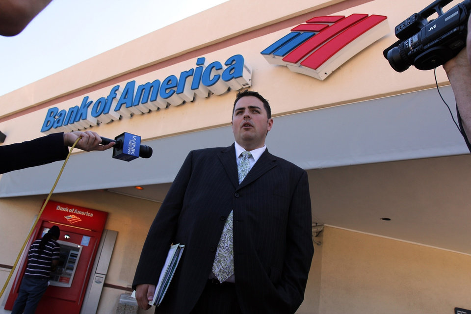 Photo -   In this June 3, 2011 photo, Todd Allen, attorney for Warren and Maureen Nyerges, speaks to the media outside a Bank of America branch on Davis Boulevard, in Naples, Fla., while deputies meet with the bank manager inside. Bank of America tried to foreclose on the Nyerges' fully-paid, Golden Gate Estates home last year, starting a legal battle with the couple, who had paid cash for the home in 2009. (AP Photo/Naples Daily News, Eric Strachan) FORT MYERS OUT; MAGS OUT