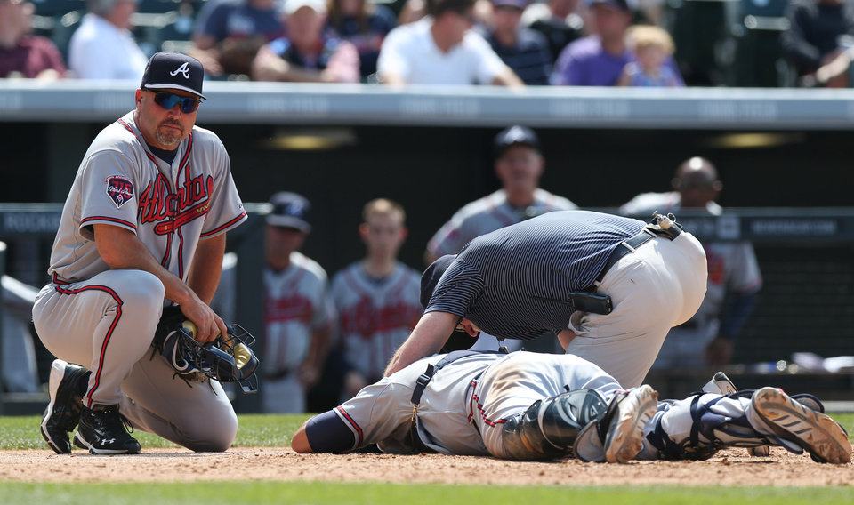 Photo - Atlanta Braves manager Fredi Gonzalez, left, looks on as catcher Gerald Laird, center, is tended to by trainer Jeff Porter after Laird was hit in the face on a swing by Colorado Rockies' Corey Dickerson in the eighth inning of the Rockies' 10-3 victory in a baseball game in Denver on Thursday, June 12, 2014. Laird was forced to leave the game after the play, which was the catalyst for the ejection of Rockies manager Walt Weiss. (AP Photo/David Zalubowski)