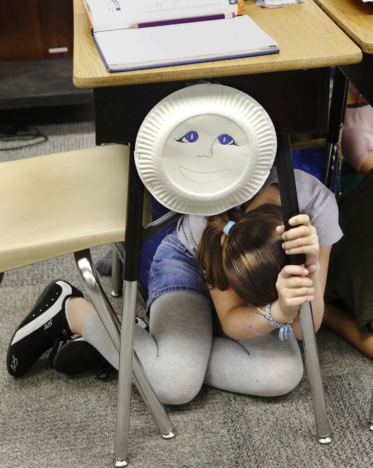 "Above: Mackenzie Golden, a fourth-grader in Melinda Jordan's classroom, takes cover under her desk. Cleveland Bailey Elementary School students participated in the ""Drop, Cover and Hold On"" earthquake drill Wednesday at the Midwest City school."