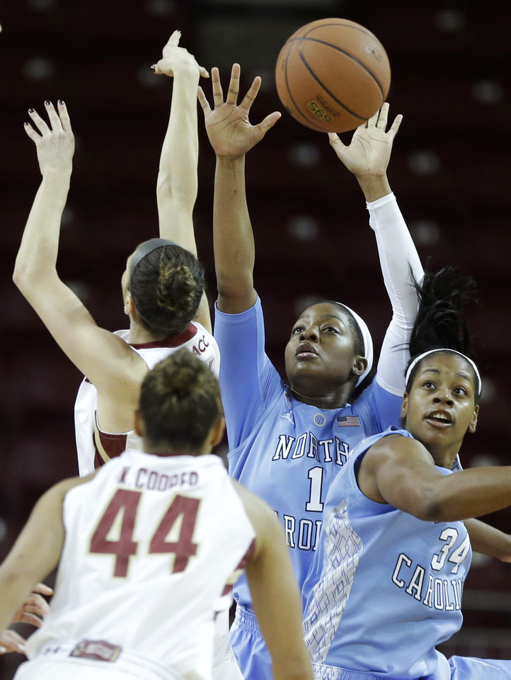 Photo - North Carolina forward Stephanie Mavunga (1) and forward Xylina McDaniel (34) vie for control of the ball with Boston College guard Kat Cooper (44) in the first half of an NCAA college basketball game on Sunday, Jan. 19, 2014, in Boston. (AP Photo/Steven Senne)