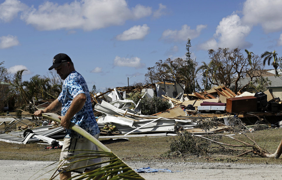 Photo - Rob Brehm cleans up debris from his home as a demolished house sits across the street after Hurricane Irma in Goodland, Fla., Tuesday, Sept. 12, 2017. (AP Photo/David Goldman)