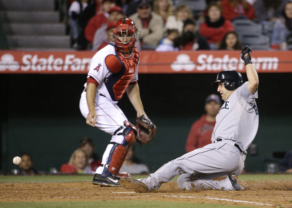 Photo - Seattle Mariners' Willie Bloomquist, right, scores on a single by Brad Miller as Los Angeles Angels catcher Chris Iannetta looks at the throw during the fifth inning of a baseball game on Wednesday, April 2, 2014, in Anaheim, Calif. (AP Photo/Jae C. Hong)