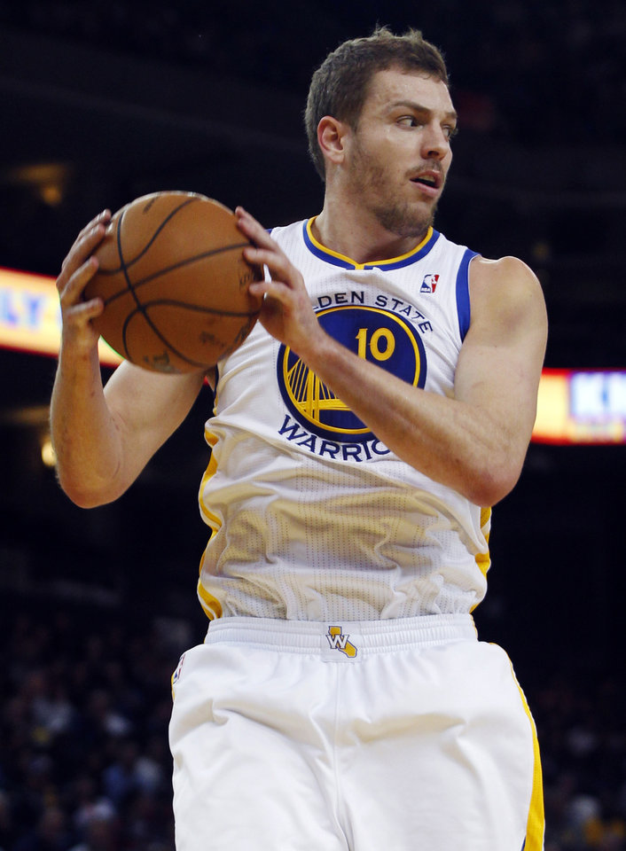 Photo - Golden State Warriors' David Lee rebounds against theToronto Raptors during the first half of an NBA basketball game in Oakland, Calif., Monday, March 4, 2013. (AP Photo/George Nikitin)