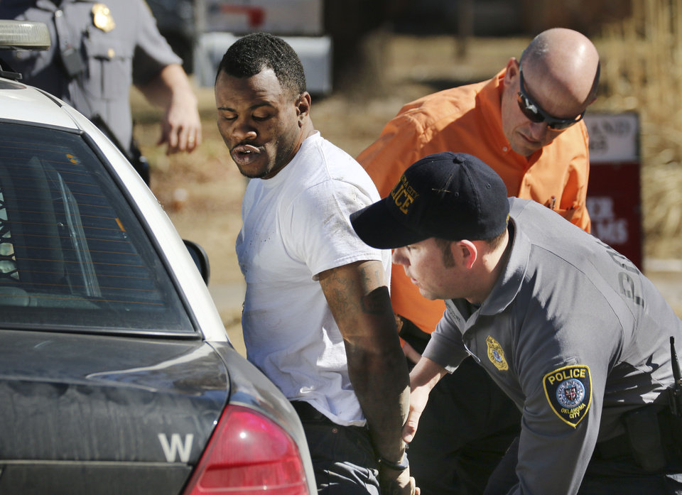 Photo - Oklahoma City police arrest a man near NW 12 and Villa Avenue after a brief chase  near Hawthorne Elementary School. The school was placed on lockdown Friday during the chase. Photo By Steve Gooch, The Oklahoman  Steve Gooch - The Oklahoman