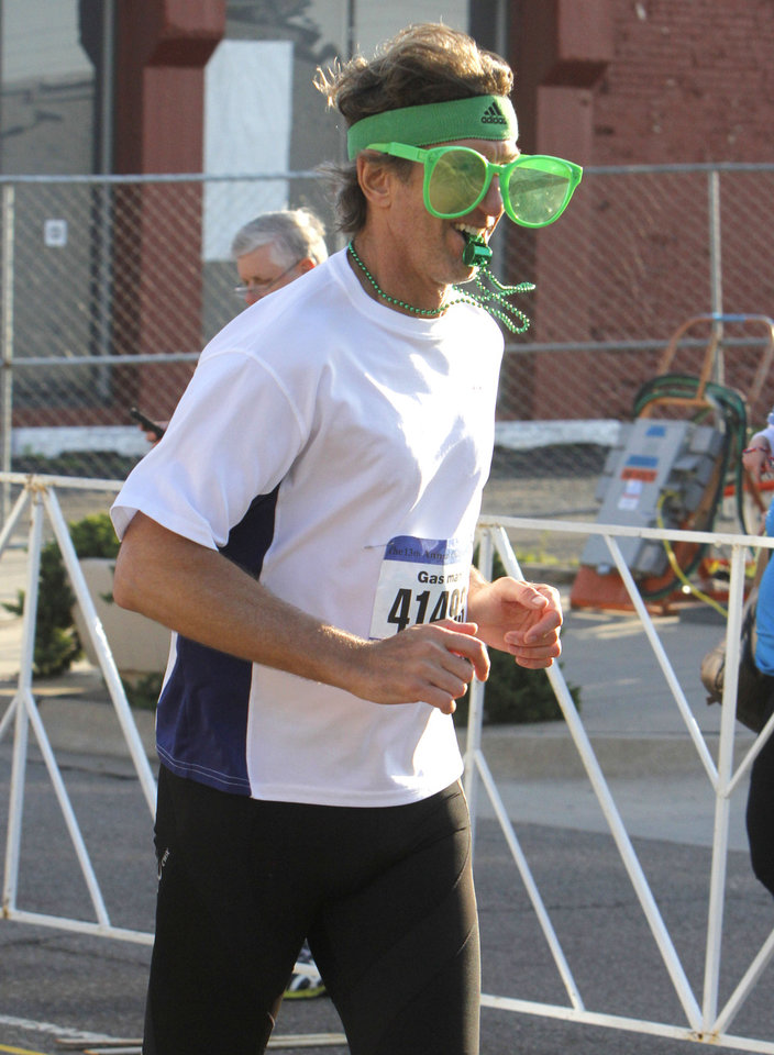 Photo - Chris Phillips wears large glasses as he finishes the half-marathon of the Oklahoma City Memorial Marathon in Oklahoma City, Sunday, April 28, 2013,  By Paul Hellstern, The Oklahoman