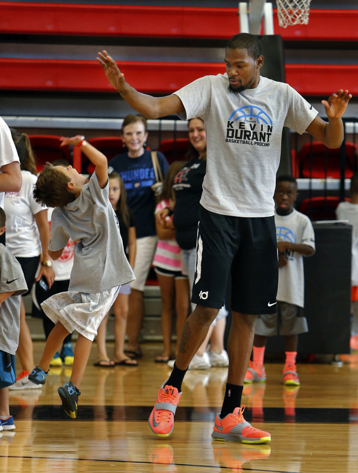Photo - James Huffmyer, 6, gives Kevin Durant a high five during Durnat's basketball camp on Thursday, Aug. 7, 2014 in Moore, Okla. Photo by Steve Sisney, The Oklahoman