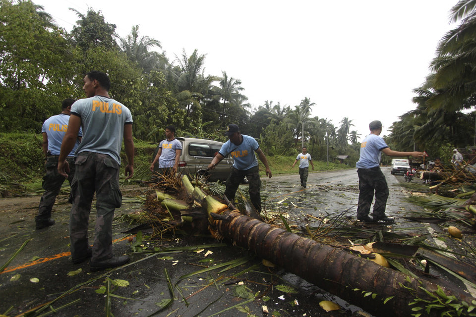 Photo - Philippine National Police clear a highway of toppled coconut trees after Typhoon Bopha made a landfall in Compostela Valley in southeastern Philippines Tuesday Dec. 4, 2012. A Philippine governor says at least 33 villagers and soldiers have drowned when torrents of water dumped by the powerful typhoon rushed down a mountain, engulfing the victims and bringing the death toll from the storm to about 40. (AP Photo/Karlos Manlupig)