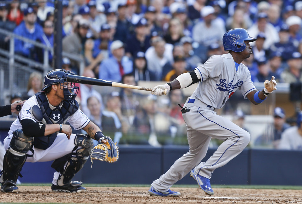 Photo - Los Angeles Dodgers' Dee Gordon slaps a base hit to center to drive in a run against the San Diego Padres in the fourth inning of a baseball game Tuesday, April 1, 2014, in San Diego.  (AP Photo/Lenny Ignelzi)
