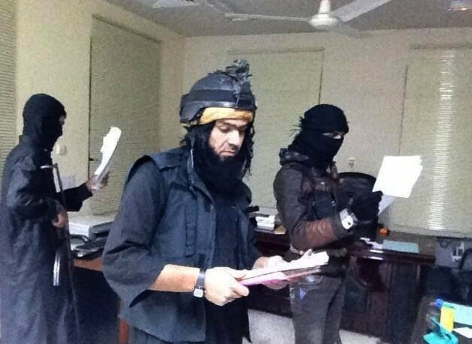 Photo - This undated image posted on a militant website on Jan. 4, 2014, which is consistent with other AP reporting, shows Shakir Waheib, a leader in the al-Qaida-linked Islamic State of Iraq and the Levant (ISIL), center, searching a government office in Ramadi, in Iraq's Anbar Province. With al-Qaida linked fighters and allied tribal gunmen camped on the outskirts, a tentative calm took hold over Fallujah on Friday, Jan. 10, 2014 and residents started to return to the besieged city west of Baghdad. Government forces were stationed nearby as sporadic street fighting breaks out in other cities. The picture painted by residents, officials and international groups suggests that both the militants and government forces are preparing for a long standoff with civilians caught in the middle.(AP Photo via militant website)