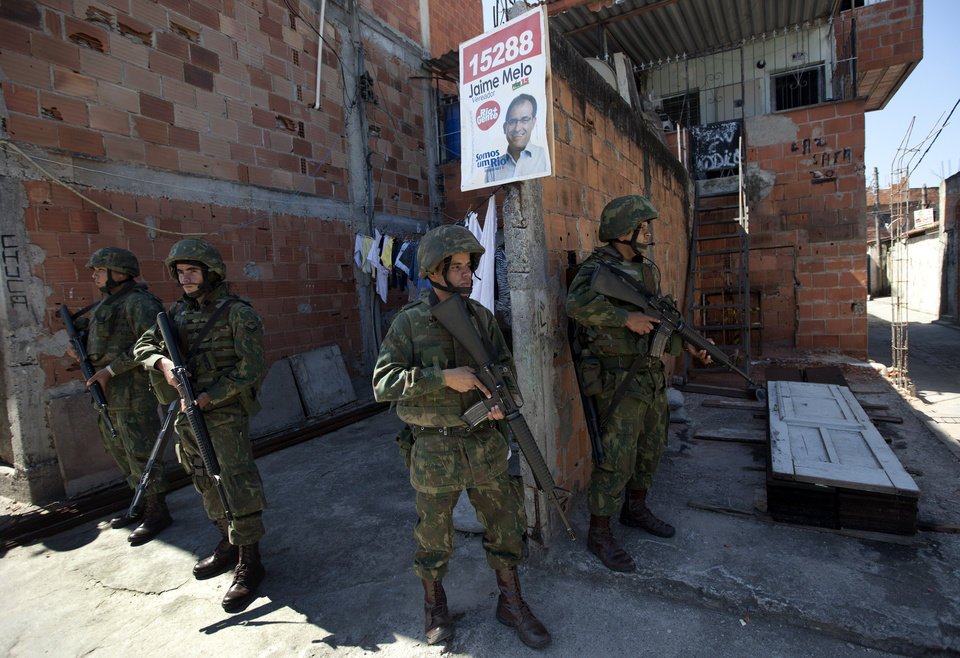 In this Oct. 1, 2012 photo, soldiers stand guard in the Fogo Cruzado slum where an election campaign sign hangs ahead the municipal elections in Rio de Janeiro, Brazil. Brazil will hold nationwide municipal elections on Sunday, Oct. 7. (AP Photo/Silvia Izquierdo)