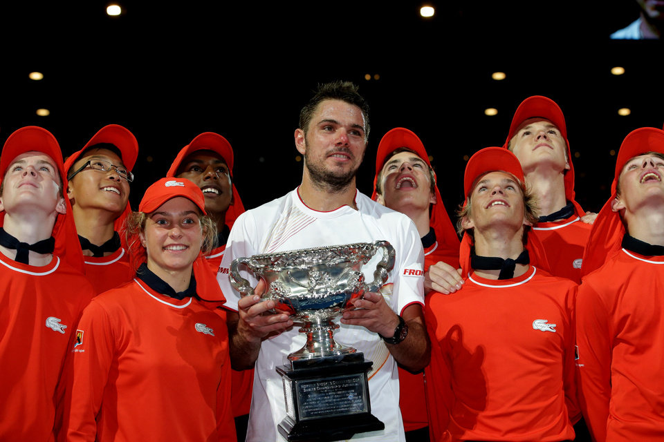 Photo - Stanislas Wawrinka of Switzerland poses with the trophy, along with ball boys and girls,  after defeating Rafael Nadal of Spain in the men's singles final at the Australian Open tennis championship in Melbourne, Australia, Sunday, Jan. 26, 2014. (AP Photo/Aaron Favila)