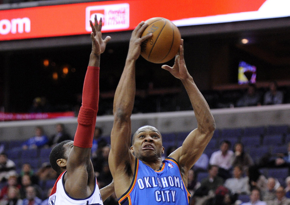 Oklahoma City Thunder guard Russell Westbrook (0) goes to the basket against Washington Wizards guard John Wall, left, during the first half of an NBA basketball game on Wednesday, Jan. 18, 2012, in Washington. (AP Photo/Nick Wass) ORG XMIT: VZN104