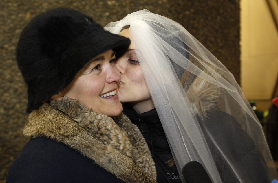Photo - Amy Andrews, right, smiles as she wears a veil while kissing her partner Jeri Andrews while waiting to be among the first to be issued a marriage licenses to a same-sex couple, Wednesday, Dec. 5, 2012, in Seattle. King County Executive Dow Constantine was to began issuing the licenses just after midnight, immediately upon certification of the November election that passed Referendum 74 allowing same-sex couples to wed. Amy Andrews wore the same veil during a symbolic, though not legal, marriage ceremony the couple had in 2011. (AP Photo/Elaine Thompson)