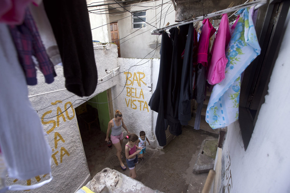 Photo - In this May 25, 2013 photo, a woman walks with her children as they leave the Bela Vista Bar in the Pavao-Pavaozinho slum in Rio de Janeiro, Brazil. Whole sections of some favelas are accessible only via steep staircases, and restaurant owners in the slums say the tricky logistics of keeping ingredients in stock is among their biggest challenges.  (AP Photo/Victor R. Caivano)