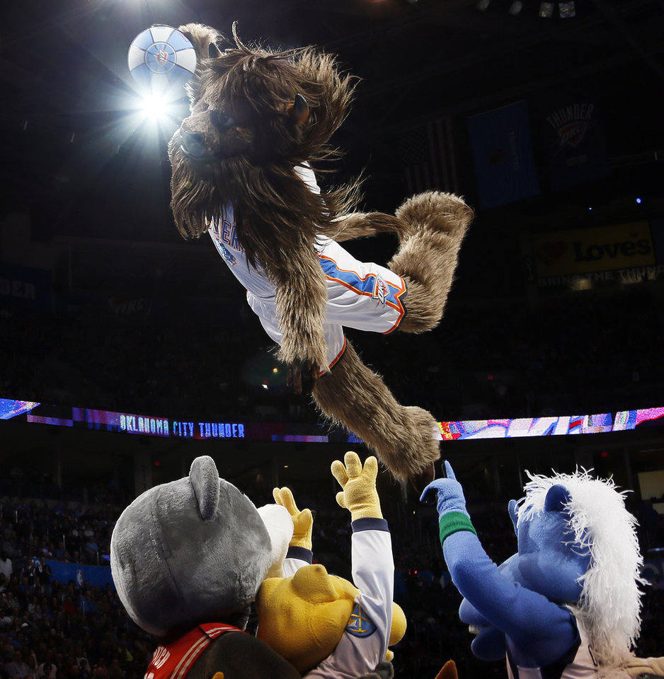 Photo - Oklahoma City mascot Rumble the Bison dunks over other NBA mascots in attendance during an NBA basketball game between the Oklahoma City Thunder and Minnesota Timberwolves at Chesapeake Energy Arena in Oklahoma City, Friday, Feb. 22, 2013. Photo by Nate Billings, The Oklahoman