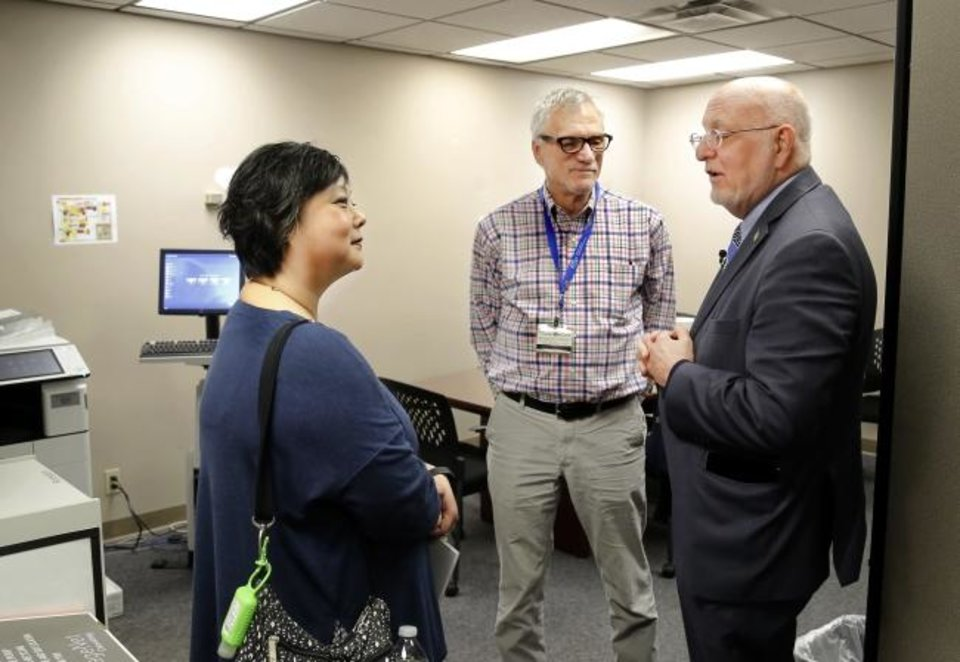Photo -  Dr. Robert Redfield, director of the Centers for Disease Control and Prevention, right, talks to Dr. Michelle Salvaggio, medical director, and Dennis Creedon, a client advocate, in March during a tour of the HIV clinic at OU Medicine. [Jim Beckel/The Oklahoman]