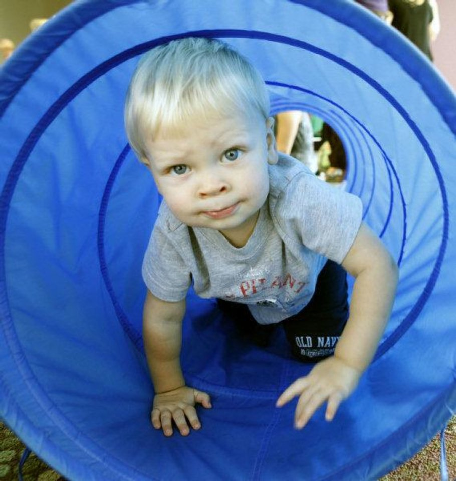 Connor Nevitt, 1, emerges from a tunnel during Lapsit: Playtime and Story Time at the Edmond Library. PHOTO BY PAUL HELLSTERN, THE OKLAHOMAN <strong>PAUL HELLSTERN</strong>