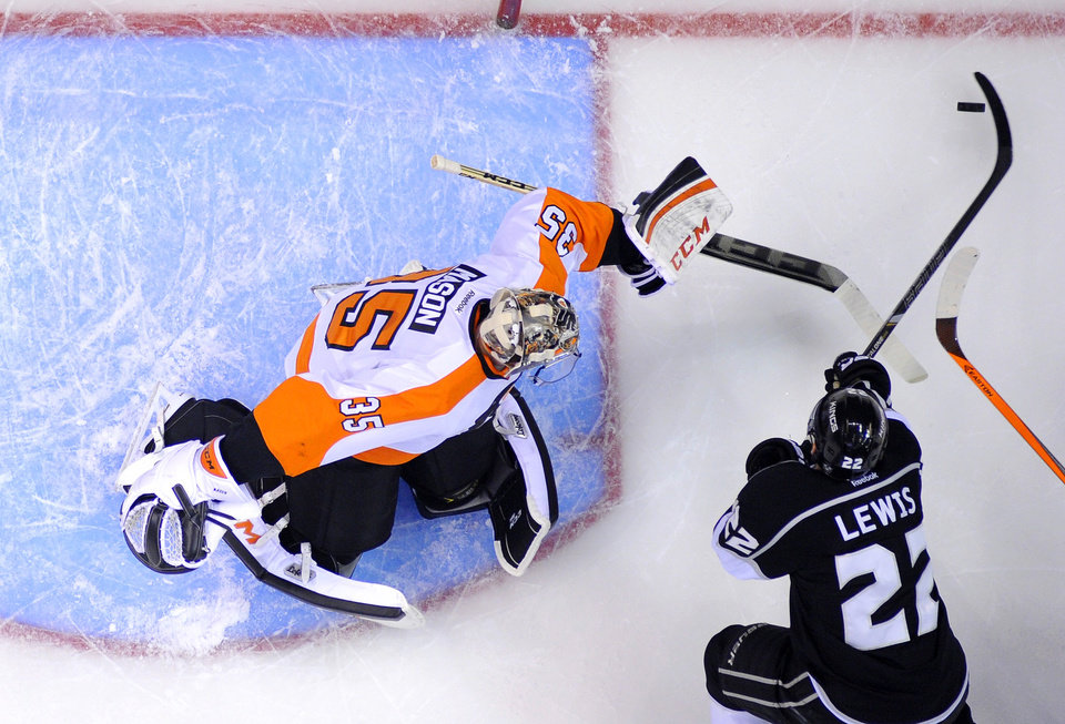 Photo - Los Angeles Kings center Trevor Lewis, right, tries to get a shot in on Philadelphia Flyers goalie Steve Mason during the first period of an NHL hockey game, Saturday, Feb. 1, 2014, in Los Angeles. (AP Photo/Reed Saxon)