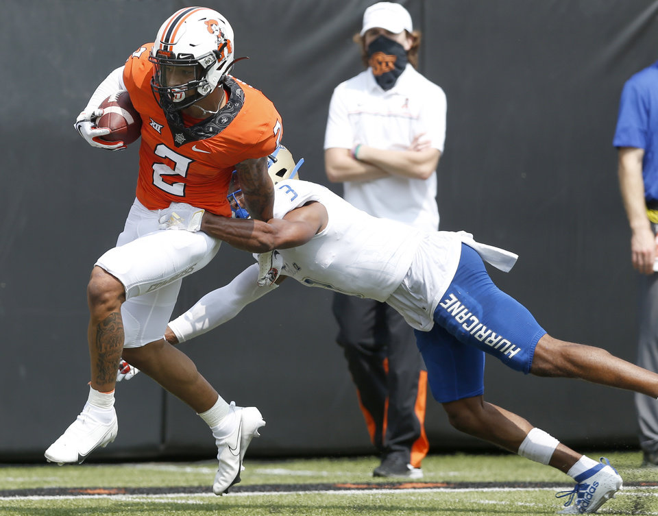 Photo - Oklahoma State's Tylan Wallace takes the ball close to the end zone at the end of the third quarter before he is brought down by Tulsa's Cristian Williams during the second half of the season opener at Boone Pickens Stadium in Stillwater on Saturday. [JOHN CLANTON, TULSA WORLD]