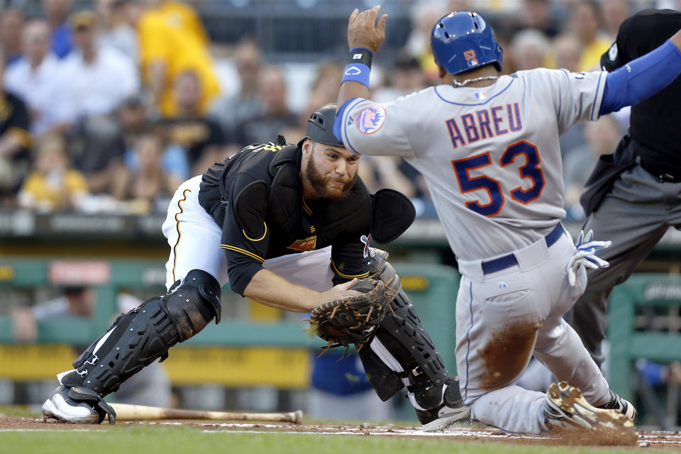 Photo - Pittsburgh Pirates catcher Russell Martin, left, prepares to tag out New York Mets' Bobby Abreu for the third out as Abreu tried to score from second on a hit by Ruben Tejada in the second inning of a baseball game Thursday, June 26, 2014, in Pittsburgh. (AP Photo/Keith Srakocic)