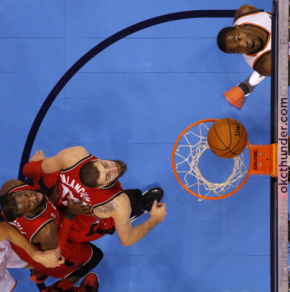 Photo - Oklahoma City's Kevin Durant (35) watches his shot goes in as Toronto's Jonas Valanciunas (17) and DeMarre Carroll (5) watch during an NBA basketball game between the Oklahoma City Thunder and the Toronto Raptors at Chesapeake Energy Arena on Wednesday, Nov. 4, 2015. Photo by Bryan Terry, The Oklahoman