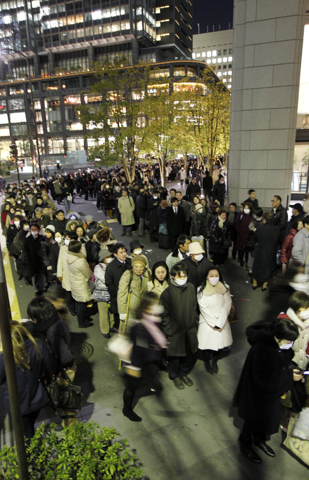 Photo - People wait for buses at a bus terminal near Tokyo railway station as train and bus services are suspended due to a powerful earthquake Friday, March 11, 2011. The largest earthquake in Japan's recorded history slammed the eastern coasts Friday. (AP Photo/Hiro Komae) ORG XMIT: TTX106