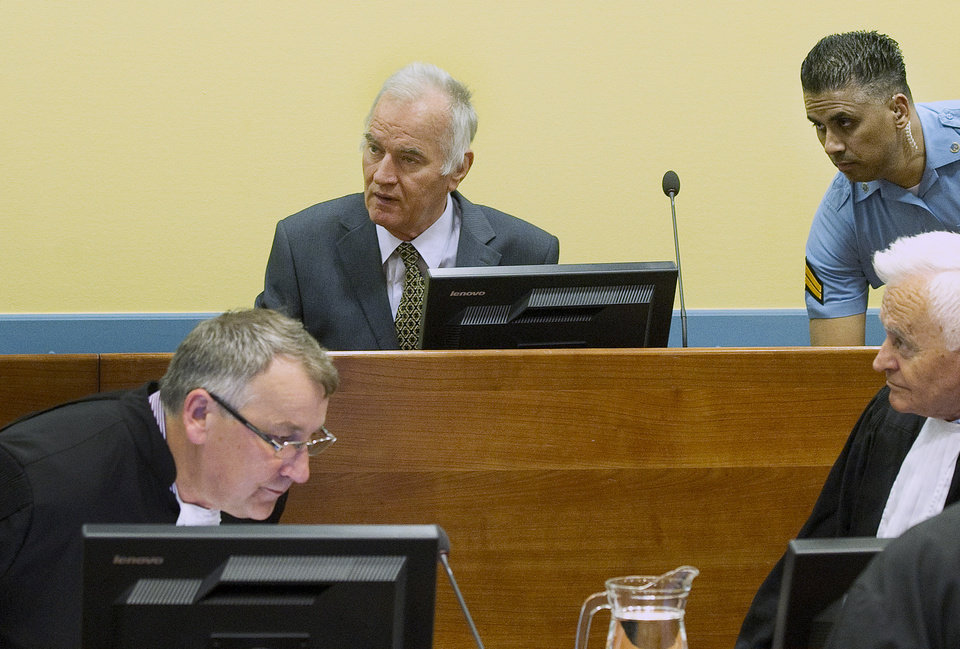 Photo -   Former Bosnian Serb military commander Gen. Ratko Mladic, center rear, a UN security guard, rear right, and member of his defense, front, are seen at the start of his trial at the Yugoslav war crimes tribunal in The Hague, Netherlands, Wednesday May 16, 2012. Twenty years after the opening shots of the Bosnian War, Mladic has gone on trial on charges of genocide, crimes against humanity and war crimes, his appearance at the UN tribunal marks the end of a long wait for justice to survivors of the 1992-95 war that left some 100,000 people dead. (AP Photo/Toussaint Kluiters, Pool)