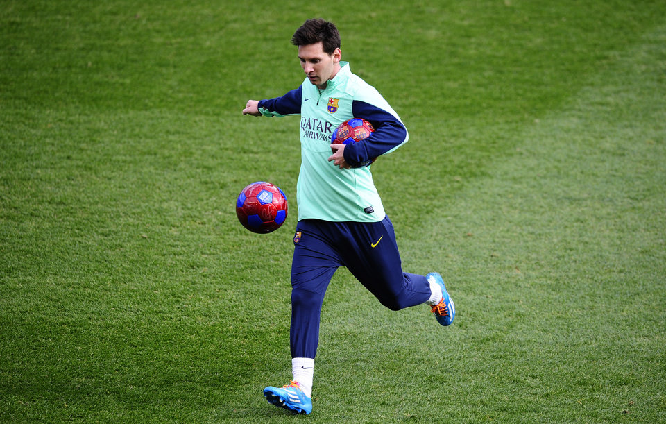 Photo - FC Barcelona's Lionel Messi, from Argentina, kicks the ball during a training session at the Mini Stadi Stadium in Barcelona, Spain, Friday, Jan. 3, 2014. (AP Photo/Manu Fernandez)