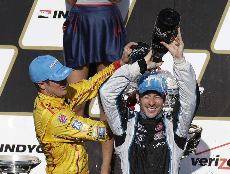 Photo - Simon Pagenaud, right, of France, pours sparkling wine over his head as he celebrates winning the inaugural Grand Prix of Indianapolis IndyCar auto race with second-place finisher Ryan Hunter-Reay at the Indianapolis Motor Speedway in Indianapolis, Saturday, May 10, 2014. (AP Photo/Darron Cummings)