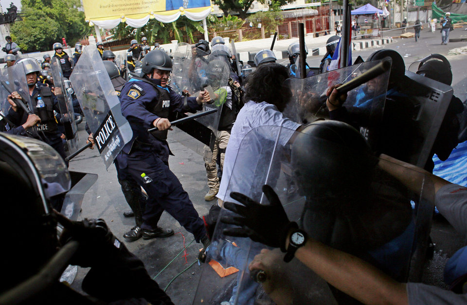 Photo - Riot police beat an anti-government protester during a clash in Bangkok, Thailand, Tuesday, Feb. 18, 2014. Emergency medical officials said that one civilian was killed and 50 people were injured in clashes between Thai police and anti-government protesters in Bangkok. Multiple gunshots were heard midday Tuesday at the site in a historic section of town near the Government House, but it wasn't clear who was firing. (AP Photo/Wally Santana)