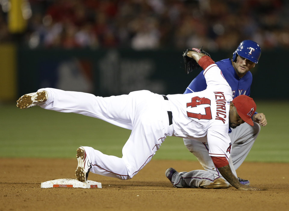 Los Angeles Angels second baseman Howie Kendrick(47) falls to the ground after forcing out Texas Rangers' A.J. Pierzynski during the seventh inning of a baseball game in Anaheim, Calif., Monday, April 22, 2013. (AP Photo/Jae C. Hong)